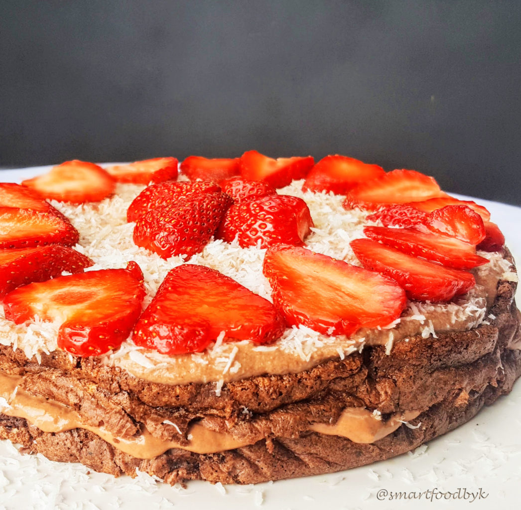 Low-calorie dark chocolate cake with coconut cream and strawberries
