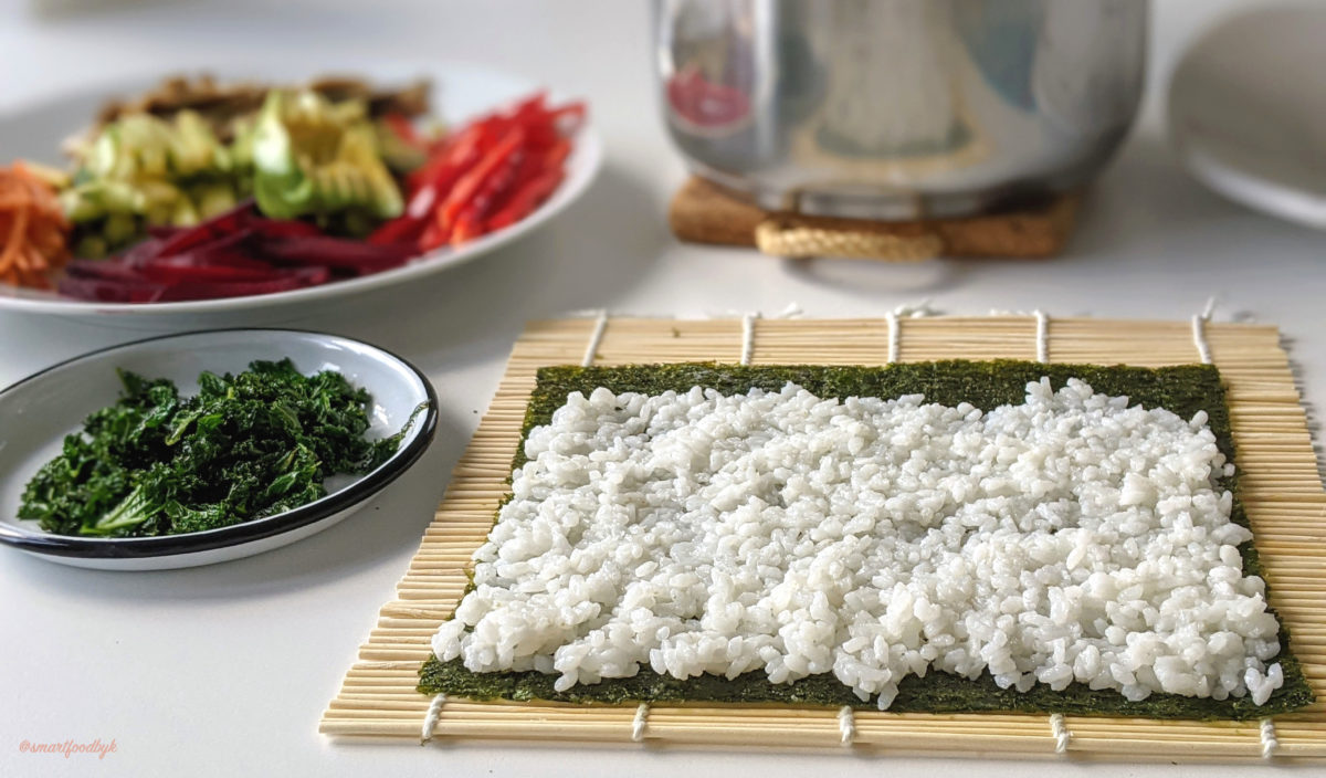 Sushi rice spread on a nori sheet on a bamboo rolling mat.